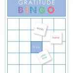 "Caption reads: Gratitude Bingo. Shows blank bingo game board with blue free space in center. Three scattered sample cards include ""books, home, play time."""