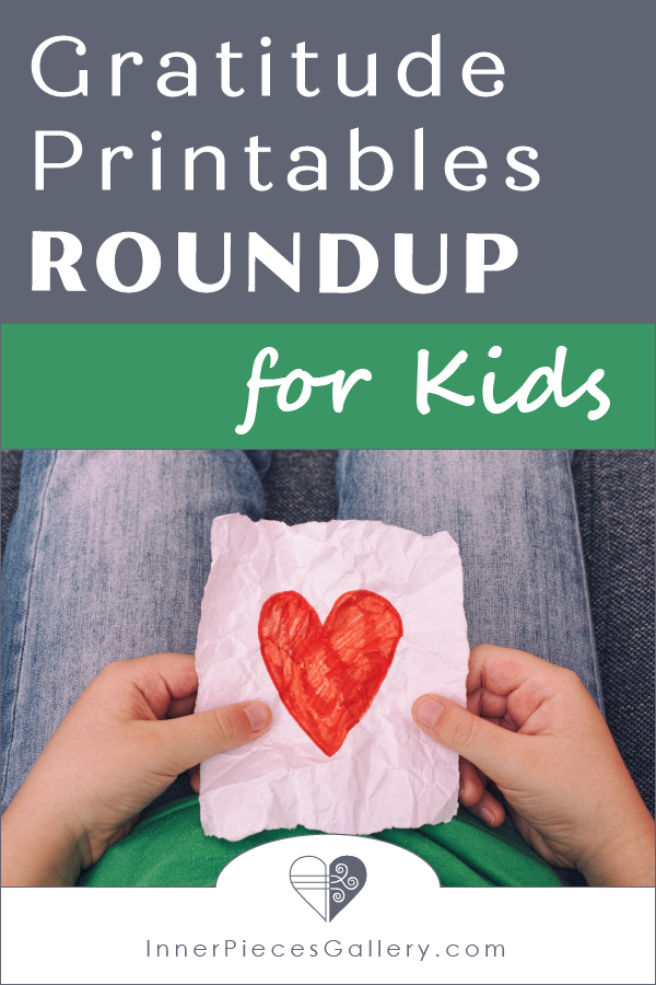 Boy in green shirt and jeans holding a drawing of a red heart. Caption reads: Gratitude Printables Roundup for Kids.