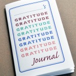 """Cover of printable gratitude journal for kids. Word """"gratitude"""" repeated 8 times in various colors. Blue border. Place to write child's name at the top."""